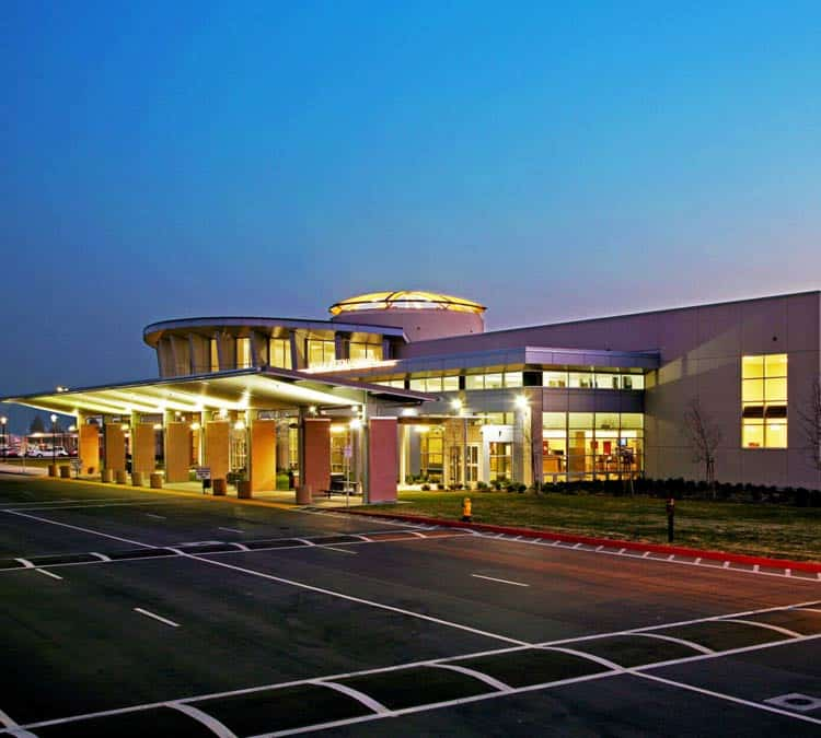 Image of Meadows Field airport terminal at dusk. The image shows the outside of the building in front of an empty street