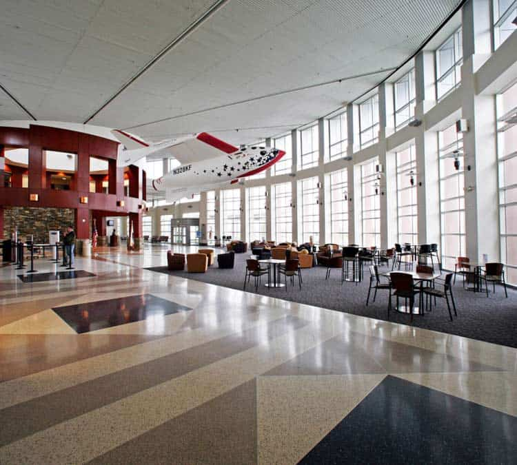 Image of Meadows Field Airport terminal. It's the interior of the building with a wall of windows, lots of seating, and a coffee shop