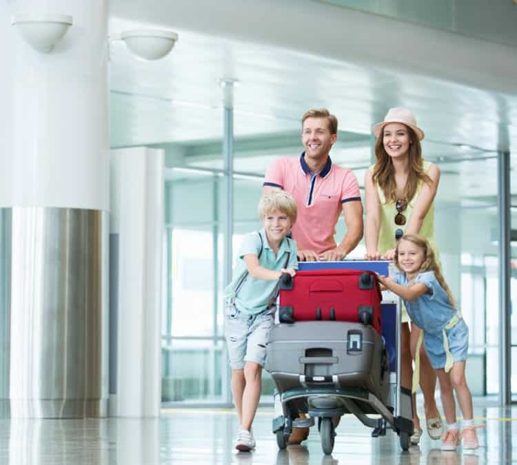 Image of mother, father, daughter & son holding a luggage cart. They are happy and excited to be at Meadows Field airport.