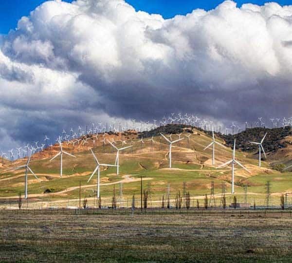 Image of the hills in California with windmills scattered all over. The sky is blue and there are big fluffy clouds.
