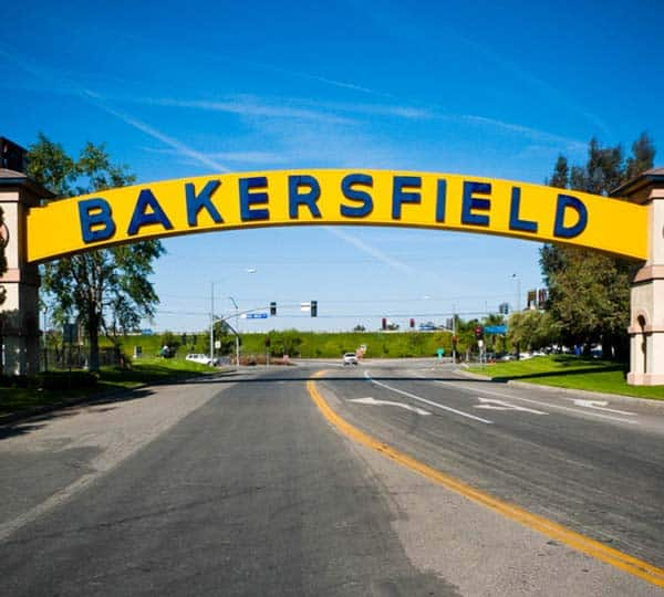 "Sign over the street saying ""Backersfield"". The sign is in yellow with blue letters and is arched from one side to the other."